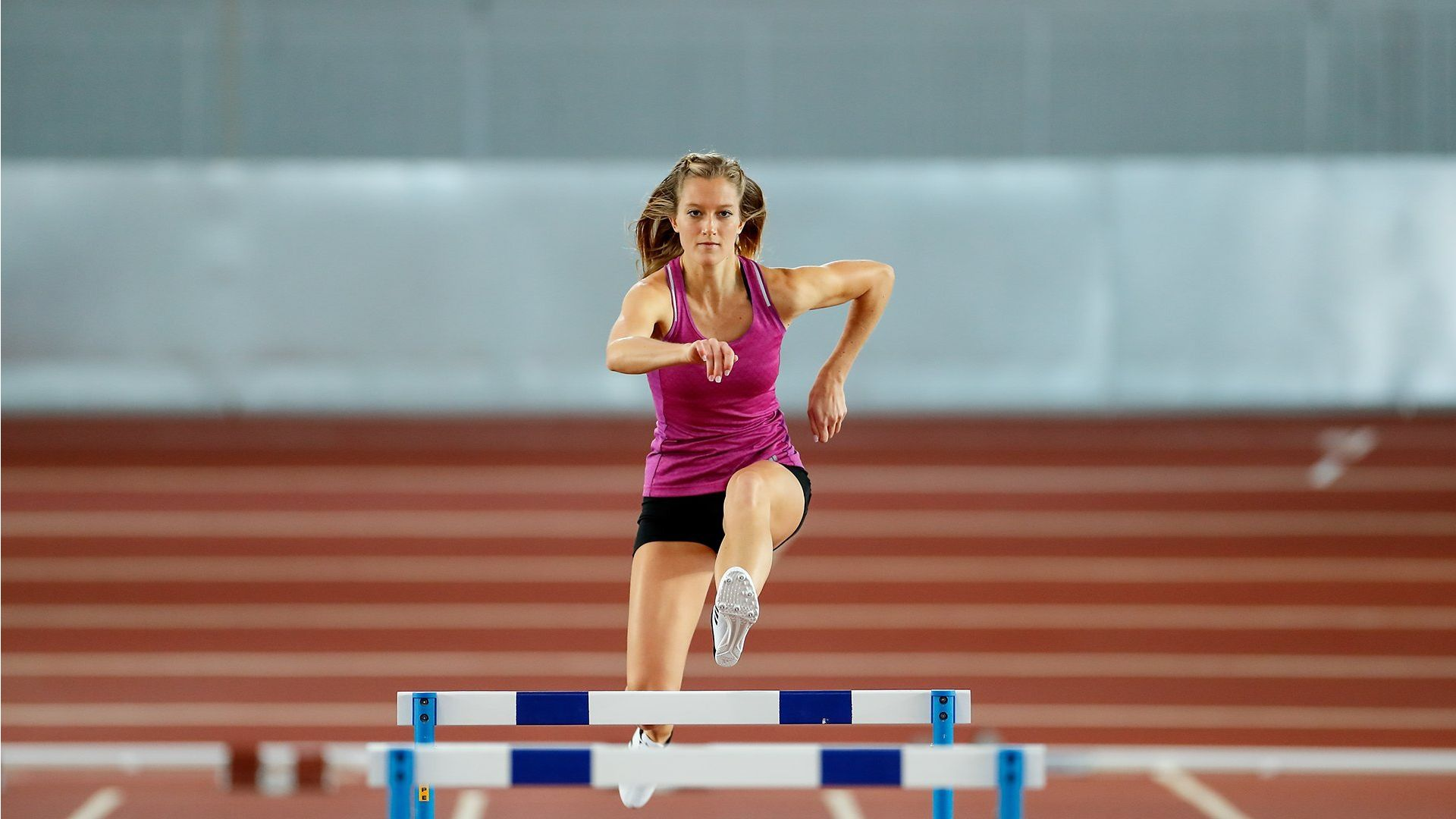 woman jumping over hurdles in sprint
